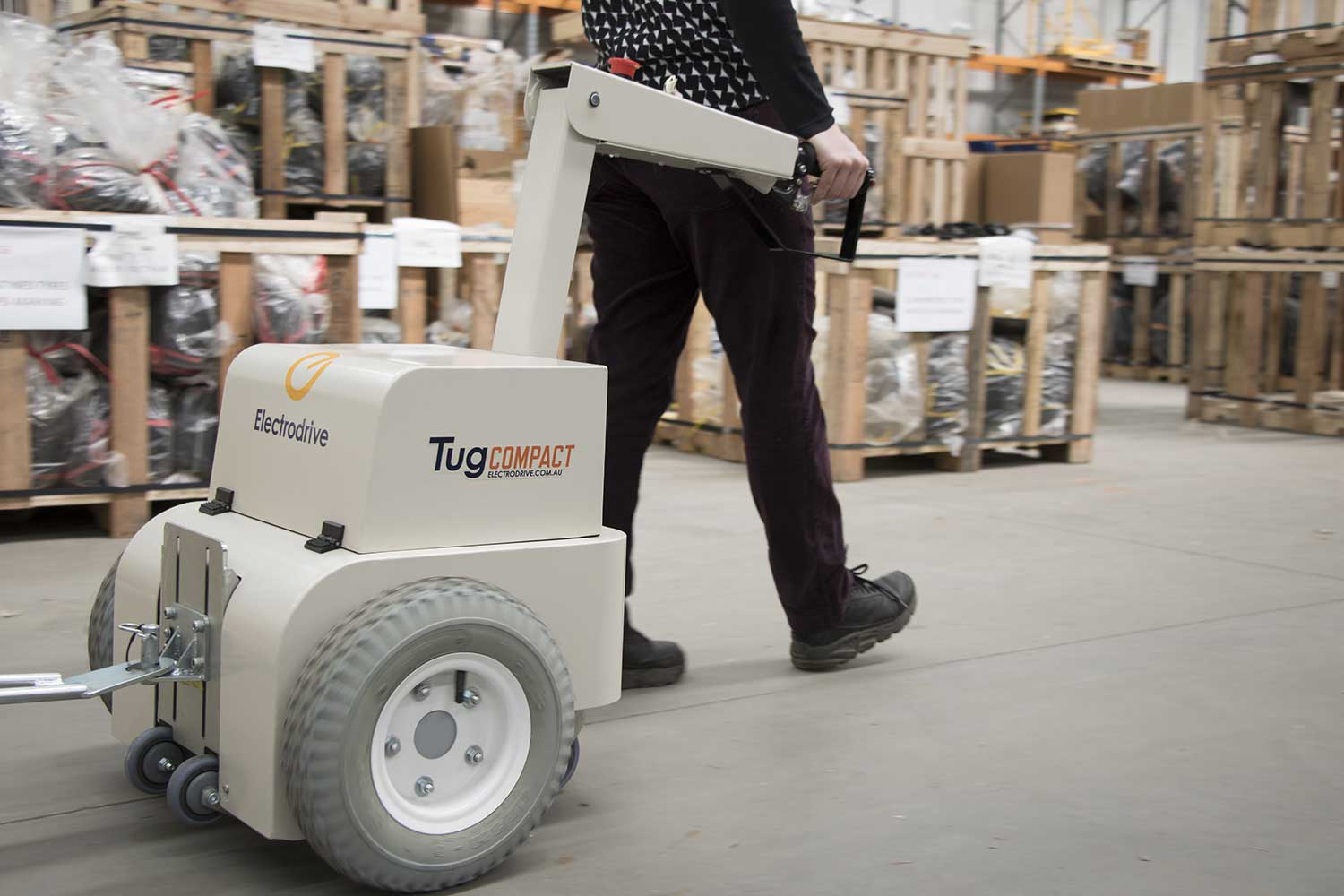 Electrodrive's Tug Compact towing heavy boxes in a warehouse