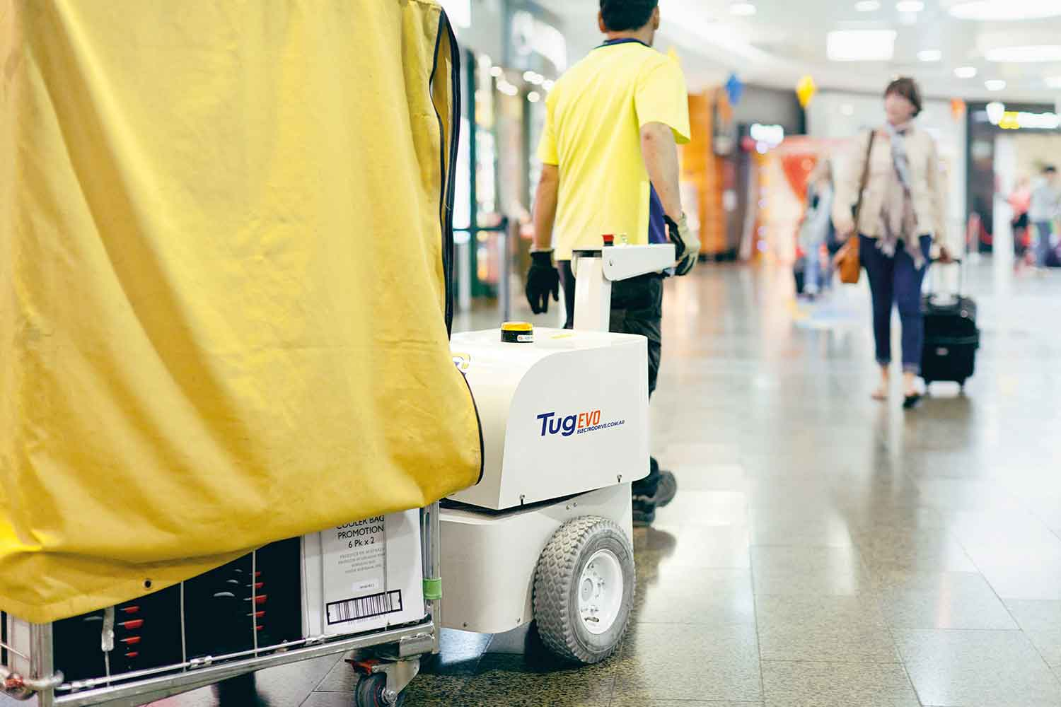 Electrodrive's Tug Evo towing a large trolley through an airport